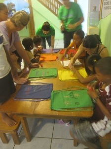The children help decorate bags for distributing supplies to families in need